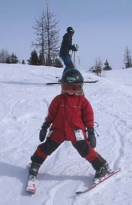 Young child downhill skiing.